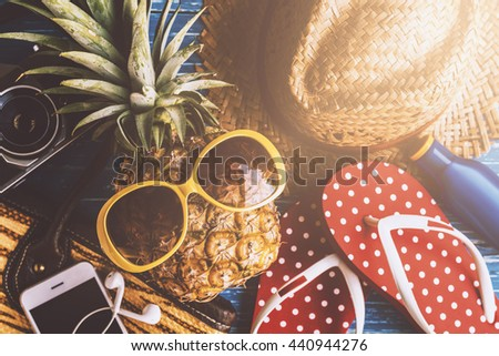 Summer concept with pineapple and essentials of traveler, Vacation background with beach items on wood table