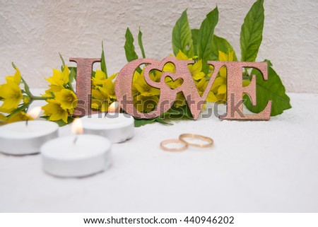 Delicate bouquet of flowers with wedding rings and candles with the word love made of wood. Wedding decor trends #440946202