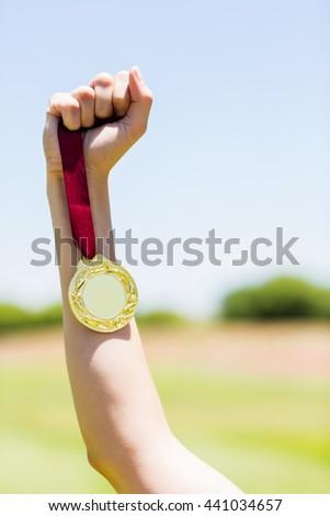 Hand of female athlete holding gold medal in stadium #441034657