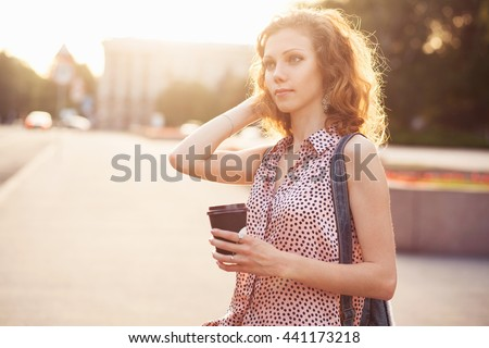 Young lovely woman walking around the city with a cup of tea #441173218