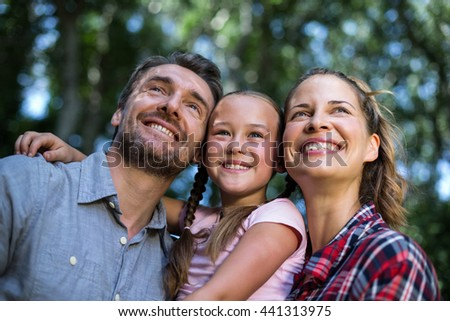 Happy parents with daughter while looking up in back yard #441313975