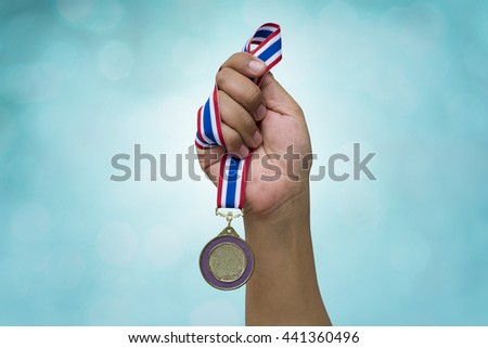 hand holding up a gold trophy cup as a winner in a competition #441360496