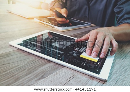 Businessman hand touching digital tablet.Photo finance manager working new Investment project office.Using new technology device.Graphic icons.Strategy business stock exchanges interface layer effect