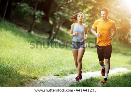Beautiful couple jogging in nature living healthy Royalty-Free Stock Photo #441441235