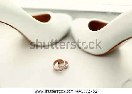 The wedding shoes stand near rings #441572752