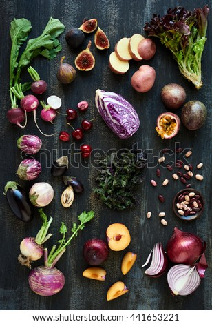 Collection of fresh purple toned vegetables and fruits on dark rustic distressed background, heirloom eggplant, fig, aubergine, cherries, radishes, lettuce, beans passionfruit, cabbage, plum, onion #441653221