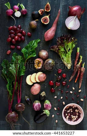 Collection of fresh purple toned vegetables and fruits on dark rustic distressed background, eggplant, beetroot, carrot, fig, aubergine, grapes, radishes, loose lettuce, beans passionfruit, cherries #441653227