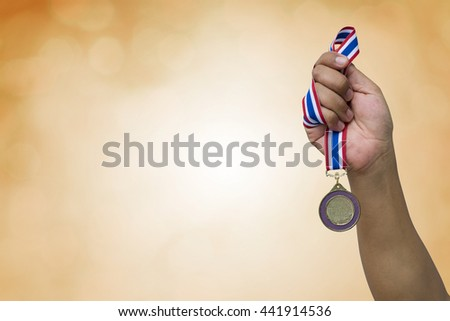 hand holding up a gold trophy cup as a winner in a competition #441914536