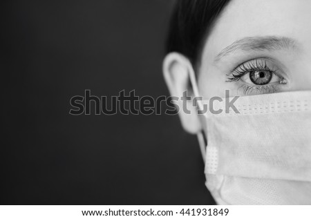 black and white art photography monochrome, red-haired girl with a medical mask on a red background, woman doctor, woman with intense look, European, half of the face, hair pinned Royalty-Free Stock Photo #441931849