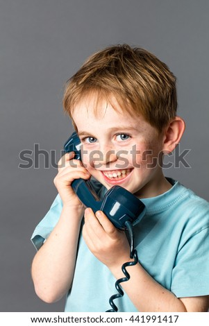 giggling 6-year old red hair boy with freckles talking on a blue old fashioned telephone for communication concept, grey background studio #441991417