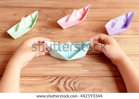 Child holds the origami ship in his hands. Colorful ships origami paper folding on a wooden table. Preschool and kindergarten paper crafts. Summer project idea  #442193344