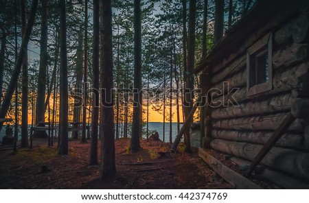 Old fishing hut in the woods on the shore of Lake Onega at sunset. #442374769