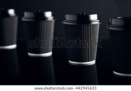 Closeup four black take away cardboard paper cups closed with caps isolated on black and mirrored. Retail mockup presentation #442945633