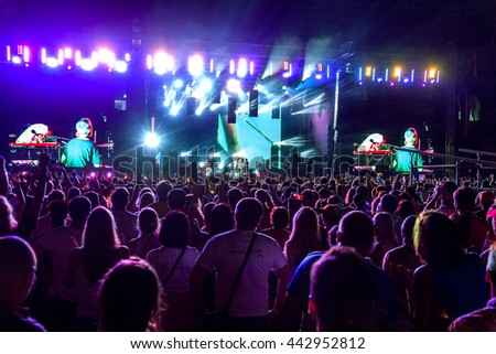 Odessa, Ukraine - June 25, 2016: A large crowd spectators having fun at stadium, at concert of Ukrainian group Ocean Elzy during creative light and music show. Cheerful bright show in the party club #442952812