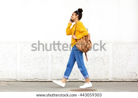 Full length side portrait of young urban woman walking and talking on mobile phone #443059303