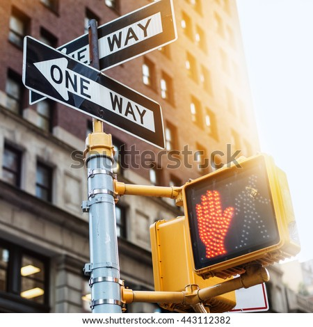 New York City road sign One Way with traffic pedestrian light on the street under sunset light. Urban city lifestyle photo.