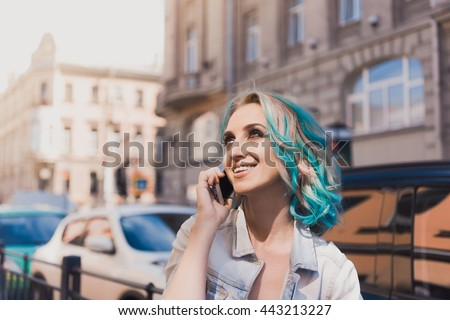 Portrait of a young beautiful bright girl hipster closeup with blue green hair with smokey ice outdoors on a sunny day in  street lifestyle in denim jacket smiling and  talking on the phone Smartphone #443213227