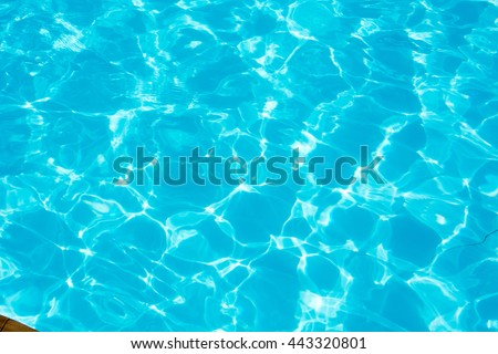 Swimming pool blue water reflecting the sun rippled details. #443320801