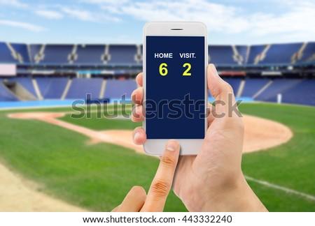 betting man through his smart phone in a baseball stadium #443332240