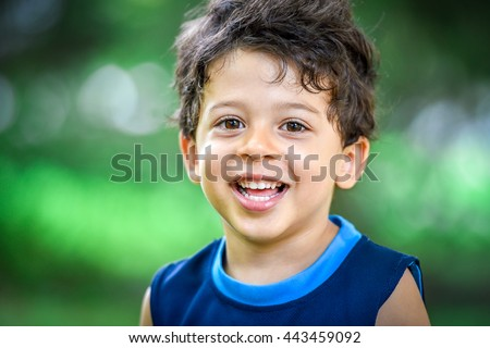 Happy mulatto boy child is smiling enjoying adopted life. Portrait of young boy in nature, park or outdoors. Concept of happy family or successful adoption or parenting. #443459092