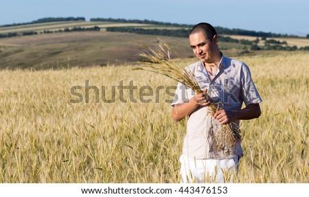 joyful young farmer in a wheat field #443476153