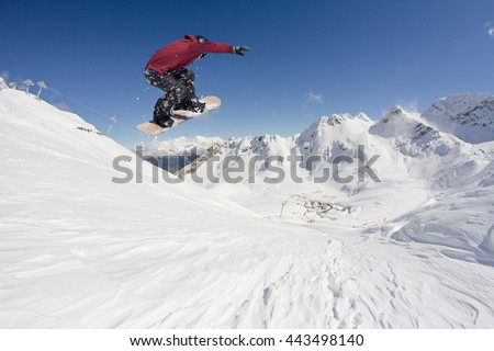 Snowboard rider jumping on mountains. Extreme snowboard freeride sport. #443498140