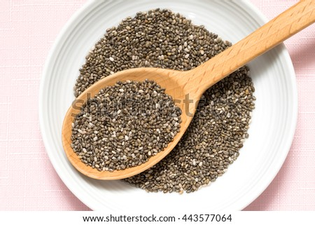 Chia seeds in a wooden spoon on pink background #443577064
