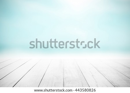 The blur cool sea background with wood floor foreground on horizon tropical sandy beach; relaxing outdoors vacation with heavenly mind view at a resort deck touching sunshine, sky surf summer clouds. #443580826