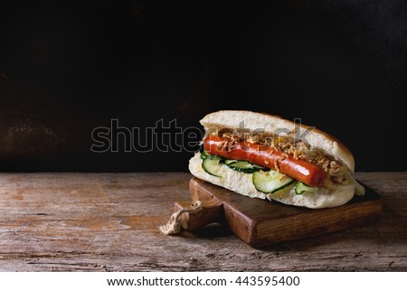 Homemade hot dog with sausage, fried onion, and cucumber, served on wood chopping board over old wooden background. Rustic style. #443595400