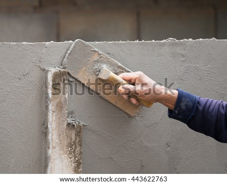 hand of builder worker use trowel plastering concrete at wall #443622763