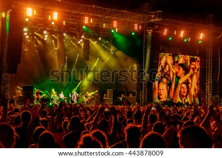 Odessa, Ukraine - June 25, 2016: Large crowd of spectators having fun at stadium, at concert of Ukrainian group Ocean Elzy during creative light and music show. Cheerful bright show in party club #443878009