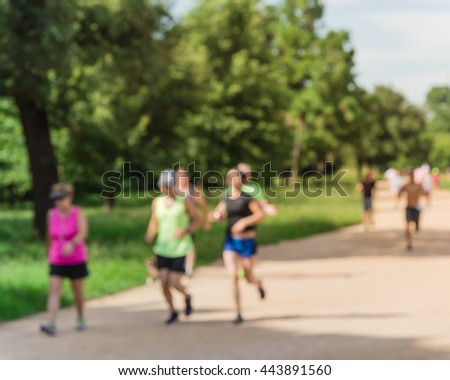 Defocused, blurred motion background of summer activities with energetic people jogging, walking, running and bicycling at green city park. Urban outdoor workout and sport. Healthy lifestyle concept. #443891560