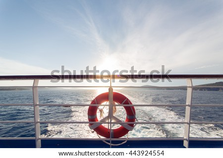 Ring life boy on big boat.Obligatory ship equipment.Personal flotation device.Prevent drowning.Orange lifesaver on the deck of a cruise ship.Traveling to an island Royalty-Free Stock Photo #443924554