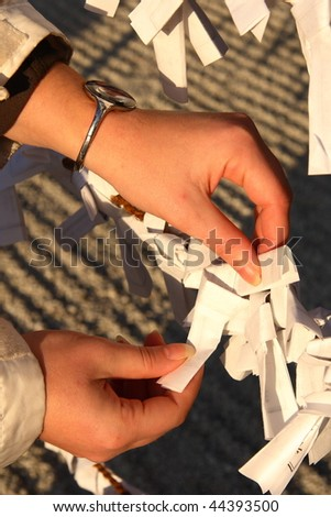 Attaching of a paper with wishes in a japanese shrine. New year celebration. #44393500
