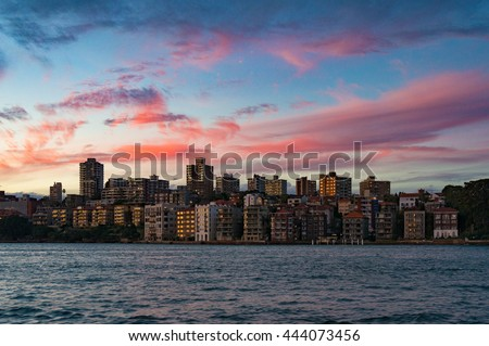 Cityscape with dramatic colorful evening sky on the background. Modern buildings of Kirribilli suburb of North Sydney, Australia. Urban sunset landscape with space for text Royalty-Free Stock Photo #444073456