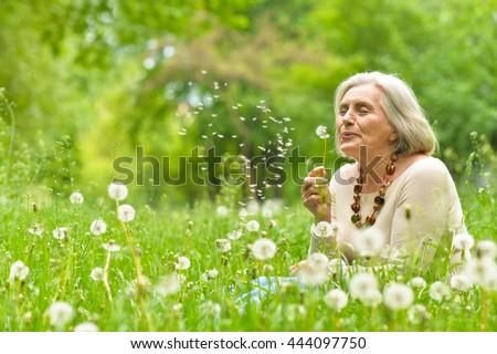 Senior woman in green park #444097750