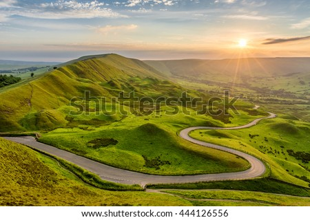 Long and winding rural road leading through green hills in the Peak District, UK at sunset. #444126556