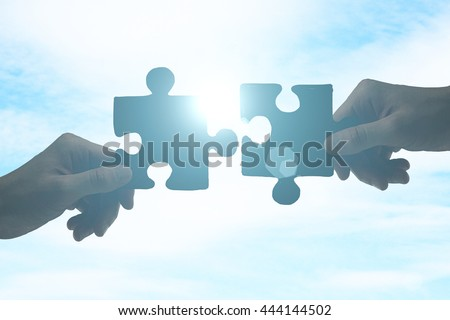 Partnership concept with hands putting puzzle pieces together on sky background with sunlight Royalty-Free Stock Photo #444144502