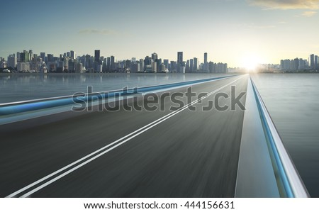 Highway overpass motion blur with city skyline background . #444156631
