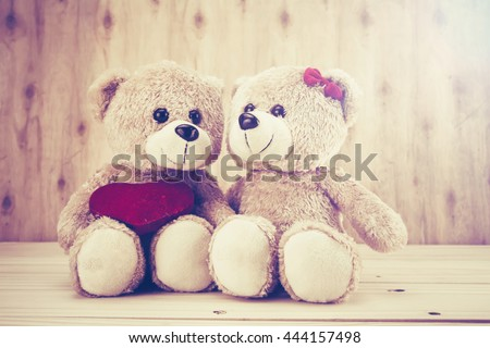 two teddy Bear with Heart on wood background,vintage tone,concept valentine