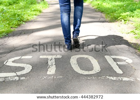 Stop sign painted on the road and female legs next to the sign. #444382972
