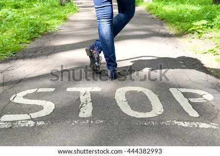 Stop sign painted on the road and female legs next to the sign. #444382993