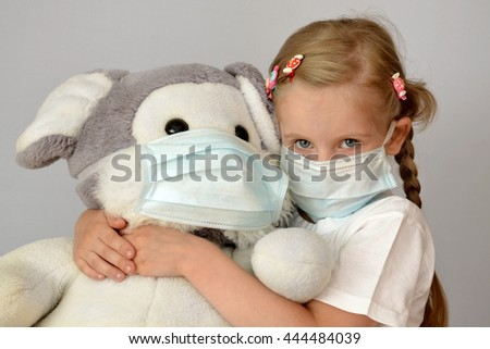 portrait of a sick child in a medical mask with a soft toy Royalty-Free Stock Photo #444484039