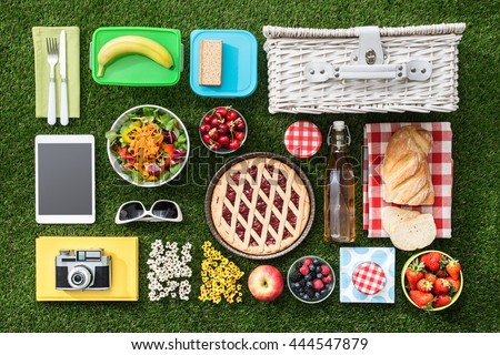 Summertime picnic on the grass with basket, salad, fruit and accessories, flat lay