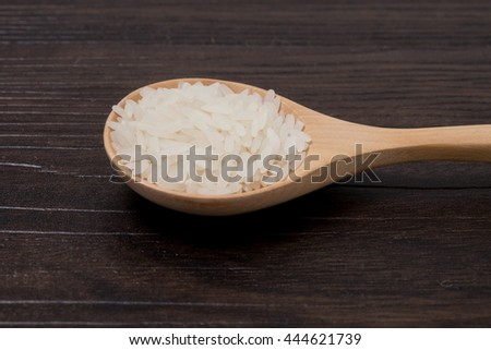 closeup White Rice on wooden spoon in brown wood background.  #444621739