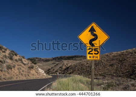 Speed limit traffic sign,25 MPH and winding road caution symbol for safety drive in the country black road,dessert mountain on the side with big blue sky with toned color and selective focus #444701266