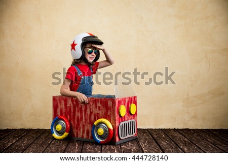 Child driving a car made of cardboard box. Kid having fun at home. Travel and summer vacation concept #444728140