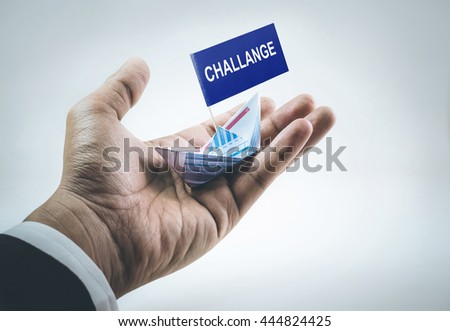 Challenge word on flag with boat made of paper graph in businessman hand.For business financial concept. #444824425