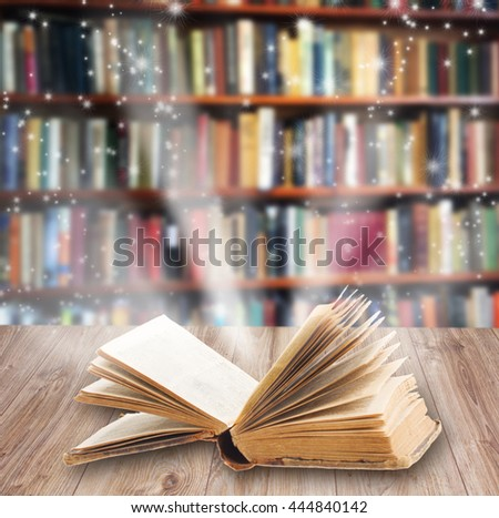 Open book on wooden book shelf with magic light  #444840142
