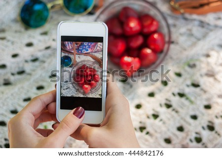 Young hipster girl taking a photo of her lunch food outdoors, chick photographing her strawberry in plate for her page on her white cell phone, modern young healthy lifestyle concept